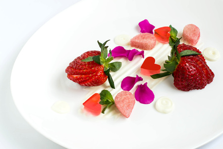 Delicious food. Dainty dessert with strawberries, cream, biscuit cake, jelly and edible petals. Easy food for ladies Stock Photo