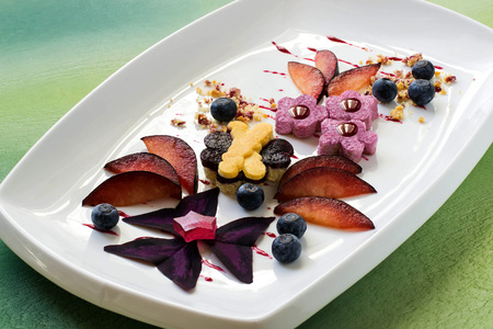 summer pudding: Elegant dessert for ladies with black plums, blueberries, cream, biscuit pie, jelly and edible petals. Exquisite food. Served for Valentines Day, Mothers Day, Womens Day Stock Photo