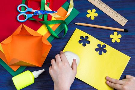 Een geschenkdoos maken door het kind. Kunstproject voor kinderen. DIY-concept. Stap-voor-stap foto-instructie. Stap 5. Kind snijbloemen met speciale perforator