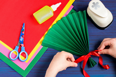 Making gift for Mothers Day by the child. Colorful bouquet of flowers out of paper. Childrens art project. DIY concept. Step-by-step photo instruction. Step 3. Child tying a bow on a paper fan Stock Photo