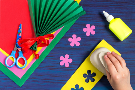 Making gift for Mothers Day by the child. Colorful bouquet of flowers out of paper. Childrens art project. DIY concept. Step-by-step photo instruction. Step 4. Child cut flowers with special puncher