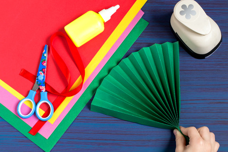 Making gift for Mothers Day by the child. Colorful bouquet of flowers out of paper. Childrens art project. DIY concept. Step-by-step photo instruction. Step 2. Child folds a fan of green paper Stock Photo