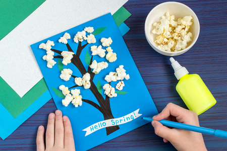 card making: Making card by a child on spring theme. Blossoming tree on a blue background. Original childrens art project. DIY concept. Step-by-step photo instruction. Step 7. Child writes: Hello spring Stock Photo