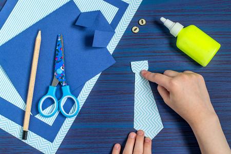 Het maken van een wenskaart voor Vaderdag. Kunstproject voor kinderen. DIY-concept. Stap-voor-stap foto-instructie. Stap 7. Kind lijmt delen van een stropdas