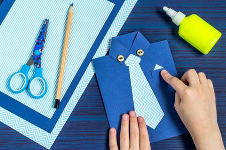 scissors: Making greeting card for Fathers Day. Childrens art project. DIY concept. Step-by-step photo instruction. Step 9. Child glues pocket and buttons