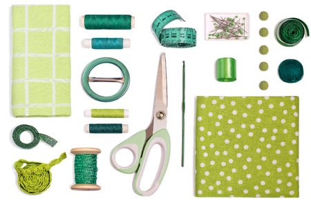 Sewing kit accessories and equipment for sewing green shades. Various sewing accessories and tools for needlework: fabric, threads, scissors, buttons, needles, braid, ribbons. Flat lay, top view