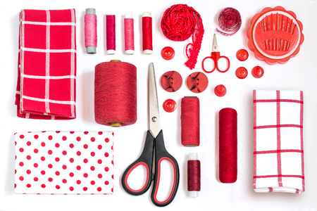 Sewing kit accessories and equipment for sewing red shades. Various sewing accessories and tools for needlework: fabric, threads, scissors, buttons, needles, braid, ribbons. Flat lay, top view