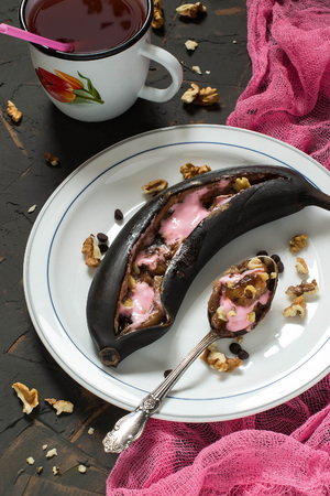 Bananas baked in peel on grill with chocolate drops and marshmallow. Black peel serves as natural pot for delicious banana dessert. Dessert is served hot, sprinkled with walnuts. Eat with spoon