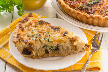 Delicious homemade quiche with cabbage and dried prunes. Vegetarian pie. Large pie and slice on plates, supplemented with fresh parsley and thyme, yellow napkin, white wooden table Stock Photo
