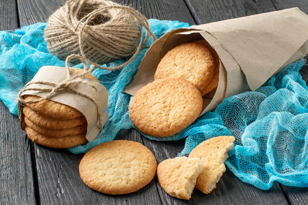 Delicious homemade cookies with onion, sesame and spices in paper bag on table with blue gauze napkin, as well as a twine for packing
