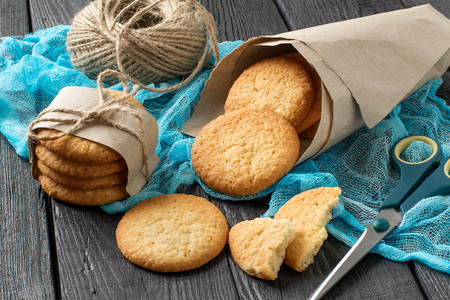 Delicious homemade cookies with onion, sesame and spices in paper bag on table with blue gauze napkin. Twine and scissors for packaging Lizenzfreie Bilder