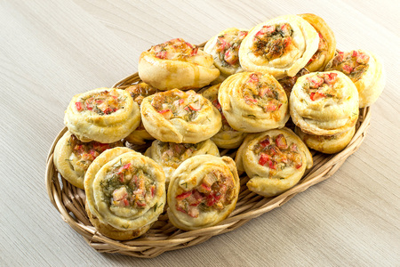 Tasty buns of puff pastry with vegetables and cheese in wicker basket on wooden background. Original form of buns as roses. Homemade baking