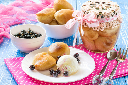 Small rich sponge cake baba, typically soaked in rum-flavored syrup. Canned sponge cake rum baba in jar. Is related to brioche and savarin. Served with ice cream, rum syrup and blackcurrant