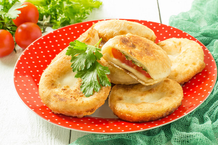 rotund: Delicious homemade pies with tomatoes, cheese, parsley and dill. Baking with vegetables. On white wooden table is a plate with pies on green napkin, fresh cherry tomatoes and lettuce Stock Photo