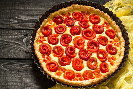 Delicious homemade pie with cheese, cottage cheese, pepper, rolled up in roll in form of flower. Large cake in baking dish on yellow gauze napkin on dark wooden table