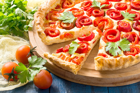 Delicious homemade pie with cheese, cottage cheese, pepper, rolled up in roll in form of flower. Large cake on wooden round plate, cherry tomatoes, parsley on yellow gauze napkin Lizenzfreie Bilder