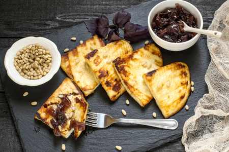 Grilled cheese, served on a slate plate with onion jam and Siberian pine nuts. Adygea cheese (Russia) is used, is prepared according to special technology. You can fry on the grill and frying pan