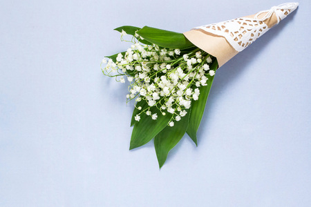 Delicate bouquet of lily of the valley (convallaria majalis) on pale blue background. Spring flowers: symbol of humility, innocence, return of happiness Lizenzfreie Bilder