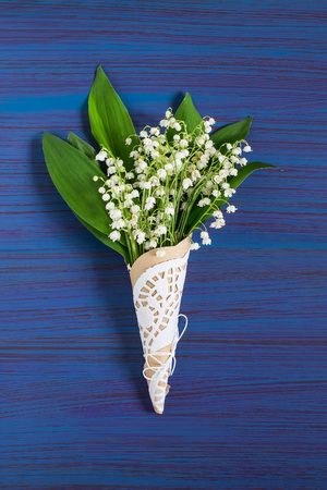 Delicate bouquet of lily of the valley (convallaria majalis) on blue background. Spring flowers: symbol of humility, innocence, return of happiness
