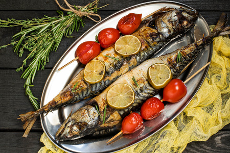 flesh colour: Mackerel or scomber cooked on brazier. Served on metal plate with lime, rosemary, baked cherry tomatoes. Plate with fish on dark wooden table with yellow gauze napkin