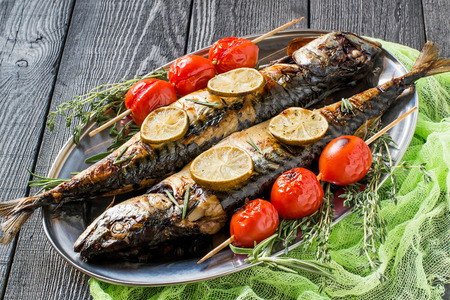 flesh eating animal: Mackerel or scomber cooked on brazier. Served on metal plate with lime, rosemary, baked cherry tomatoes. Plate with fish on dark wooden table with yellow gauze napkin