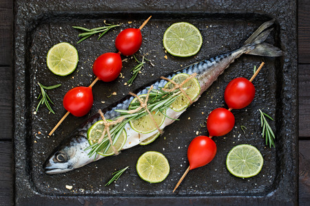 flesh eating animal: Mackerel or scomber with lime, rosemary, cherry tomatoes and spices. Preparing mackerel for baking on an old scratched iron pan
