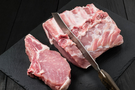 Fresh raw pork loin, knife on slate plate. Meat prepared for barbecue, roasting, stewing. Dark wooden background