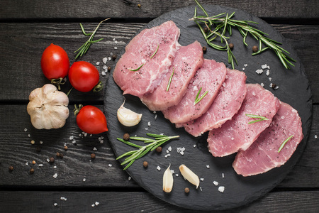 Fresh uncooked boneless pork chops on a slate plate, vegetables, herbs and spices on a dark wooden background. Meat prepared for cooking Lizenzfreie Bilder