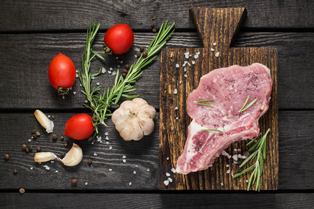 Piece of raw pork loin on old cutting board, vegetables, herbs and spices on dark wooden background. Meat prepared for cooking