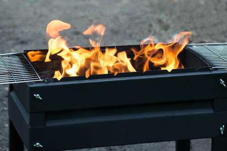Burning coals and flame in brazier on picnic. B-B-Q. Rest on nature and preparation for cooking on grill. Selective focus