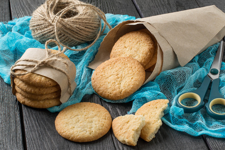 sesame cracker: Delicious homemade cookies with onion, sesame and spices in paper bag on table with blue gauze napkin, as well as a twine for packing