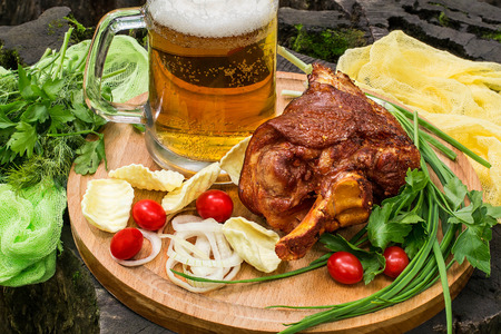 spice: Picnic. Tasty fried on grill pork knuckle, mug with beer, green and pickled onion, parsley, tomatoes, potato chips on large round board. Board with products and colored gauze napkin are on old stump