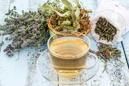 trifolium: Various dried meadow herbs and herbal tea on light old wooden table. Dried medicinal plants in bag, basket and in bundle. Preparing medicinal plants for phytotherapy and health promotion