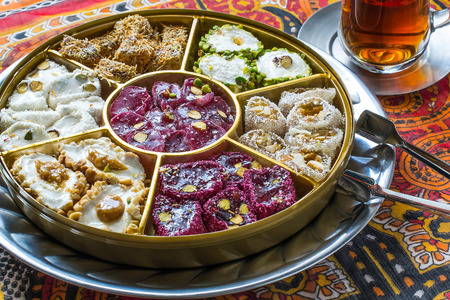 Eastern sweets. Assorted traditional Turkish delight (Rahat lokum) on background with national ornaments. Turkish delight with different nuts, coconut shavings and powdered sugar