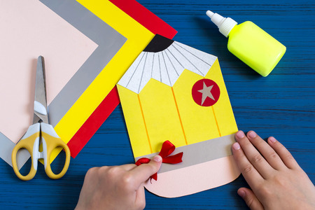 school class: Making greeting card in form of pencil for new school year. Welcome back to school. Childrens art project. DIY concept. Step-by-step photo instruction. Step 9. Child completes details of design Stock Photo