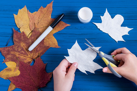 Making ghosts from maple leaves to Halloween. Halloween decor of room. Childrens art project. DIY concept. Step-by-step photo instructions. Step 3. Child carves ghost