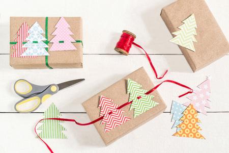 Cadeau dozen maken voor Kerstmis met je eigen handen. DIY hobby. Dozen zijn verpakt in kraftpapier, gebonden met linten met zelfgemaakte kleurrijke kerstbomen. Originele cadeau decoratie