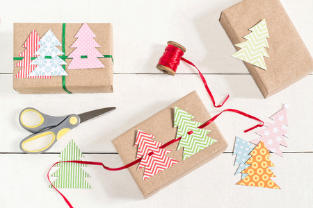 Making gift boxes for Christmas with your own hands. DIY hobby. Boxes are wrapped in kraft paper, tied with ribbons with homemade colorful Christmas trees. Original gift decoration Stock Photo