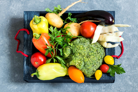 Box with various fresh vegetables on blue textured background. Organic eco bio products from farm. New harvest. Ingredient in healthy, dietary and vegetarian food. Top view Stock Photo
