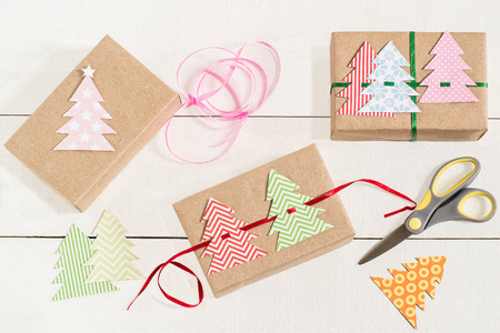 tied in: Making gift boxes for Christmas with your own hands. DIY hobby. Boxes are wrapped in kraft paper, tied with ribbons with homemade colorful Christmas trees. Original gift decoration Stock Photo