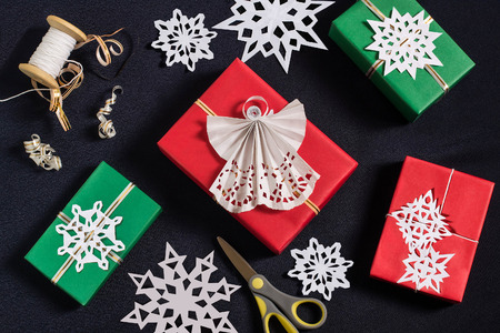 tied in: Decoration of gift boxes for Christmas with your own hands. DIY hobby. Boxes are wrapped in red and green paper, tied with ribbons with handmade snowflakes and angel. Original gift decoration Stock Photo