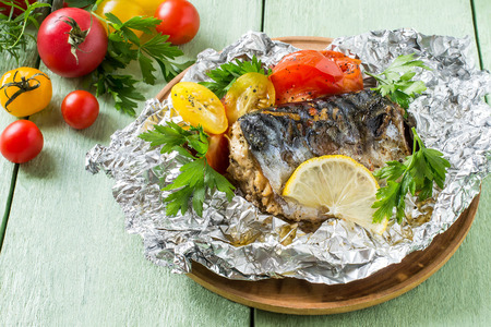 Mackerel baked with tomatoes in foil. Mackerel in foil lies on wooden plate on green wooden table. Also lie fresh tomatoes and herbs. Healthy and dietary food Stock Photo