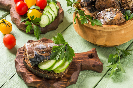 Canned food from mackerel of homemade preparation in wooden bowl. Served with fresh vegetables and herbs. Tomatoes and cucumbers on wooden board Stock Photo