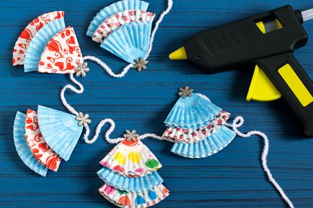 Krans maken met kerstbomen van papieren vormen voor muffins. Eenvoudige decoraties met hun eigen handen. DIY-concept. Stapsgewijze foto-instructies. Stap 5. Lijm kerstbomen op touw