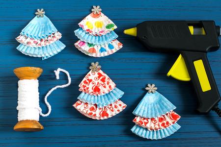 Fare ghirlande con alberi di Natale da moduli di carta per muffin. Decorazioni semplici con le proprie mani. Concetto di fai da te Istruzioni dettagliate per le foto. Passaggio 4. Crea molti alberi di Natale Archivio Fotografico - 88434339