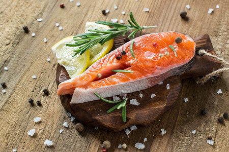 Steak of raw fresh salmon and ingredients for cooking (pepper, salt, lemon, rosemary) on small cutting board. Salmon is source of protein, Omega-Z and vitamin D. Diet and healthy food Banco de Imagens