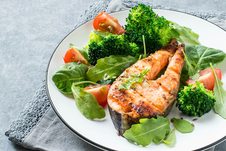 Grilled salmon steak served with tomatoes, broccoli, spinach, arugula and flaxseeds. Dietary and healthy food Archivio Fotografico