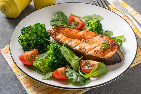 Grilled salmon steak served with tomatoes, broccoli, spinach, arugula and flaxseeds. Dietary and healthy food Imagens