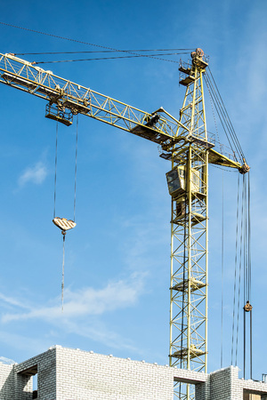 Large construction crane against sky background. Tower crane on construction site. Building under construction from white brick Stock Photo
