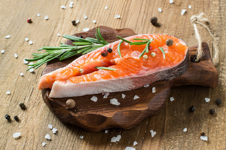 Steak of raw fresh salmon and ingredients for cooking (pepper, salt, lemon, rosemary) on small cutting board. Salmon is source of protein, Omega-Z and vitamin D. Diet and healthy food Stock Photo